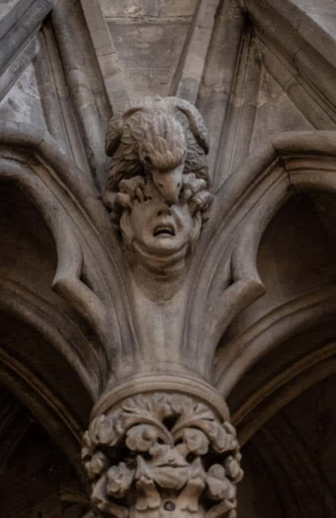 Eagle pecking out eye head carving York Minster chapter house